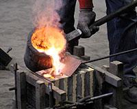 鋳型に溶かした銅を流し込む作業の写真